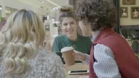 Colleagues student girls drinking coffee talking and looking at fashion items online on smartphone after shopping at the mall -. Colleagues student girls stock video footage