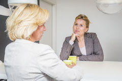Colleagues talking in the coffeebreak. Two women talking about the latest gossip on their coffeebreak in the office attentively listening to eachother royalty free stock photography