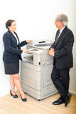 Colleagues talking at copying machine in the Royalty Free Stock Images