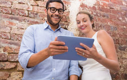 Colleagues using digital tablet against brick wall Royalty Free Stock Images
