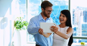 Colleagues using digital tablet. In office stock video footage