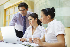 Colleagues Using Laptop In Office Stock Photo