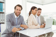 Colleagues using laptop in office Stock Image