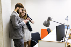 Colleagues using phone in an office Stock Photography