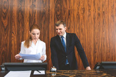 Colleagues viewing documentation at reception Royalty Free Stock Photos