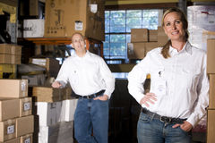 Colleagues in warehouse storage area. Two office coworkers in storage warehouse Stock Image