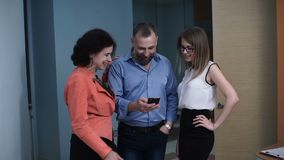 Colleagues watch the video on the smartphone and pointing to the screen are surprised. At the office stock footage