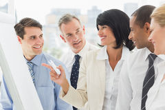 Colleagues watching happy businesswoman pointing to whiteboard Stock Photo