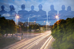 Composite image of colleagues on white background. Colleagues on white background against light trails on city street Royalty Free Stock Image
