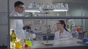 Colleagues at work talking about research and smiling. Two doctors in medical or biological lab have small talk after hard working. Woman and man in stock footage