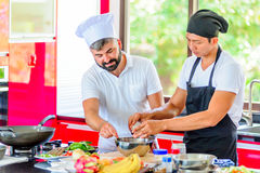 Colleagues at work: Thai and European chefs at the kitchen doing. Thai food Royalty Free Stock Photo
