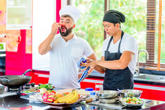 Colleagues at work: Thai and European chefs at the kitchen doing. Thai food Royalty Free Stock Image