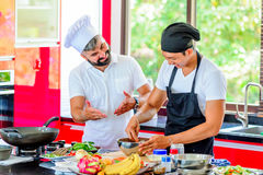 Colleagues at work: Thai and European chefs at the kitchen doing. Thai food Stock Photography