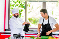 Colleagues at work: Thai and European chefs at the kitchen doing. Thai food Stock Image