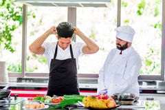 Colleagues at work: Thai and European chefs at the kitchen doing. Thai food Royalty Free Stock Photography