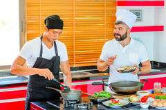 Colleagues at work: Thai and European chefs at the kitchen doing. Thai food Stock Photos