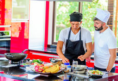 Colleagues at work: Thai and European chefs at the kitchen doing. Thai food Royalty Free Stock Images