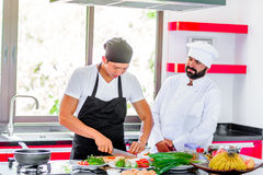 Colleagues at work: Thai and European chefs at the kitchen doing. Thai food Stock Photo