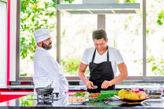Colleagues at work: Thai and European chefs at the kitchen doing. Thai food Stock Images
