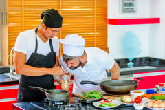 Colleagues at work: Thai and European chefs at the kitchen doing Royalty Free Stock Photo