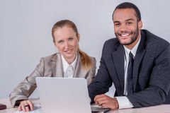 Colleagues at work. Two successful businessman smiling and looki. Ng at the laptop while businessmen sitting at a table working on a laptop on a gray background Royalty Free Stock Image