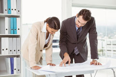 Colleagues working on blueprints at office Royalty Free Stock Photography