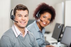 Colleagues Working In Call Center. Portrait of smiling colleagues working in call center Stock Photos