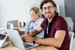 Colleagues working on startup project in office and smiling man. Looking at camera stock photography