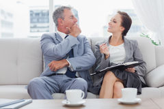 Colleagues working together sitting on sofa having coffee stock image