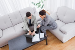 Colleagues working together sitting on sofa and using laptop Royalty Free Stock Images