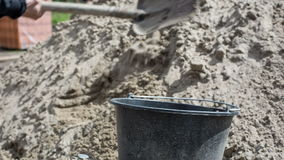 Collect concrete with a shovel in a bucket stock video