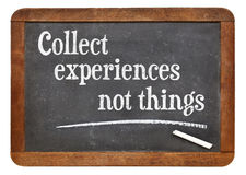 Collect experiences not things. Words of inspiration on a vintage slate blackboard royalty free stock photo