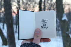 Collect moments not things. Travel idea. Book and text. Collect moments not things. Hand holding a book with the inscription stock photography