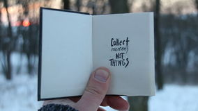 Collect moments not things. Travel idea. Book and text. Collect moments not things. Hand holding a book with the inscription stock video footage