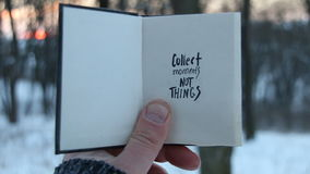 Collect moments not things. Travel idea. Book and text. Collect moments not things. Hand holding a book with the inscription stock footage