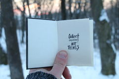 Collect moments not things. Travel idea. Book with text and snowy winter park. Collect moments not things. Hand holding a book with the inscription stock photo