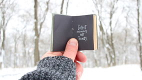 Collect moments not things. Winter Travel idea. Book and text. Collect moments not things. Hand holding a book with the inscription stock video