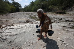 Collect water. An old woman looking for the rest of the water in a dry river bed in Boyolali, Central Java, Indonesia during the dry season royalty free stock image
