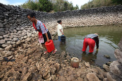 Collect water. Residents collect water for cooking purposes in a lake is almost dry during the dry season in Solo, Central Java, Indonesia Stock Photos