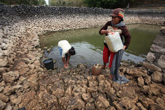 Collect water. Residents collect water for cooking purposes in a lake is almost dry during the dry season in Solo, Central Java, Indonesia Stock Photography