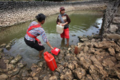 Collect water. Residents collect water for cooking purposes in a lake is almost dry during the dry season in Solo, Central Java, Indonesia Stock Photo