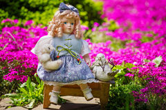 Collectable doll in the blooming garden. Beautiful collectible doll in the garden bloom Royalty Free Stock Image