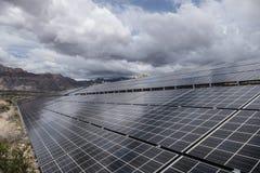 Collecte des nuages de tempête au-dessus des panneaux solaires de désert Photos stock