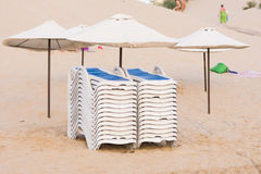 Collected in piles on beach chairs under umbrellas Stock Image