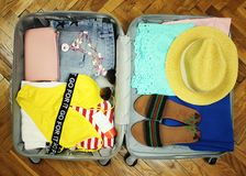 Collected suitcase for travel. Suitcase in open view closeup with things to rest on a wooden background.  stock images