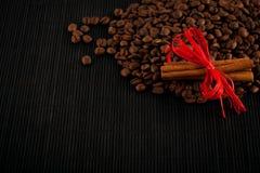 Collectes et cannelle de café sur le fond de verre de bambou noir image libre de droits