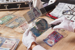 Collectible banknotes in the woman`s hand. Collectible banknotes in the plastic pocket in the woman`s hand, soft focus background Royalty Free Stock Images