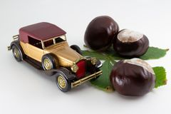 Collectibles - Horse-chestnut conkers on green leaf and vintage toy car royalty free stock photography