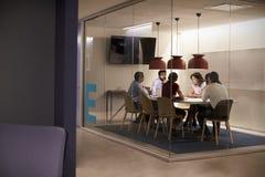 Collectief commercieel team bij lijst in een vergaderzaalcel stock fotografie