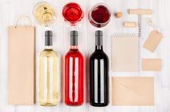 Collectief identiteitsmalplaatje voor de wijnindustrie - lege verpakking, kantoorbehoeften, wijnflessen en glazen op zachte witte Stock Foto's